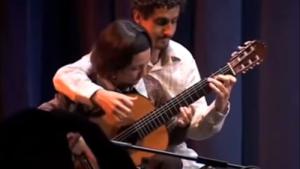 Un couple incroyablement fusionnel joue un morceau de guitare à quatre mains